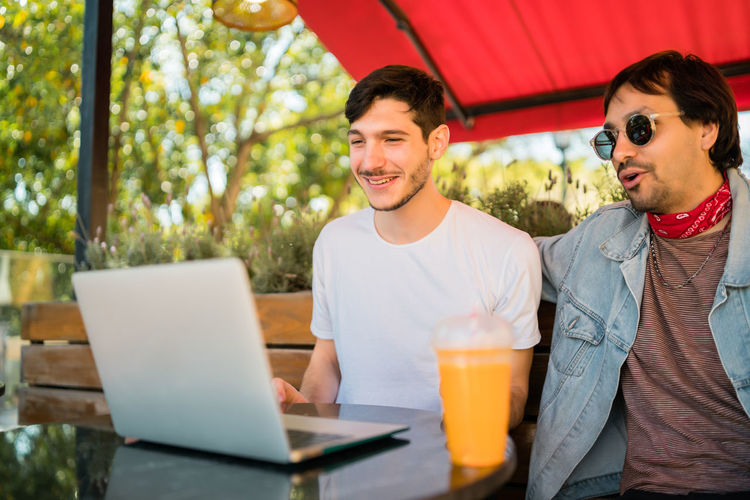 Smiling young men looking at laptop while sitting at cafe