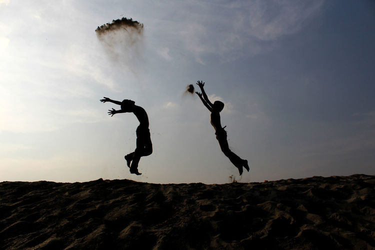 Silhouette Of Children Jumping