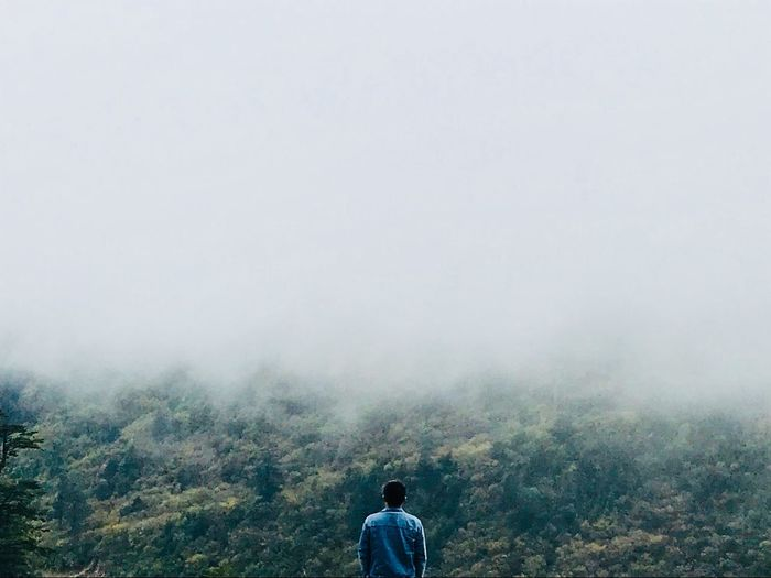 Rear view of man looking at mountain during foggy weather
