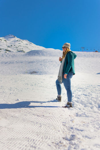 Full length of woman in warm clothes while standing on snow covered land