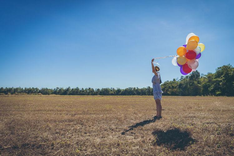 Full length of woman holding balloons on field against sky