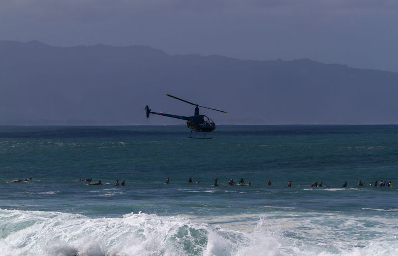 A Helicopter flying over surfers on the north shore of Oahu Hawaii Hawaii Helicopter North Shore Oahu Surf USA Aquatic Sport Beach Day Flying Group Of People Horizon Over Water Mode Of Transportation Motion Mountain Nature Ocean Outdoors Real People Sea Sky Surfers Surfing Transportation Waimea Bay Water