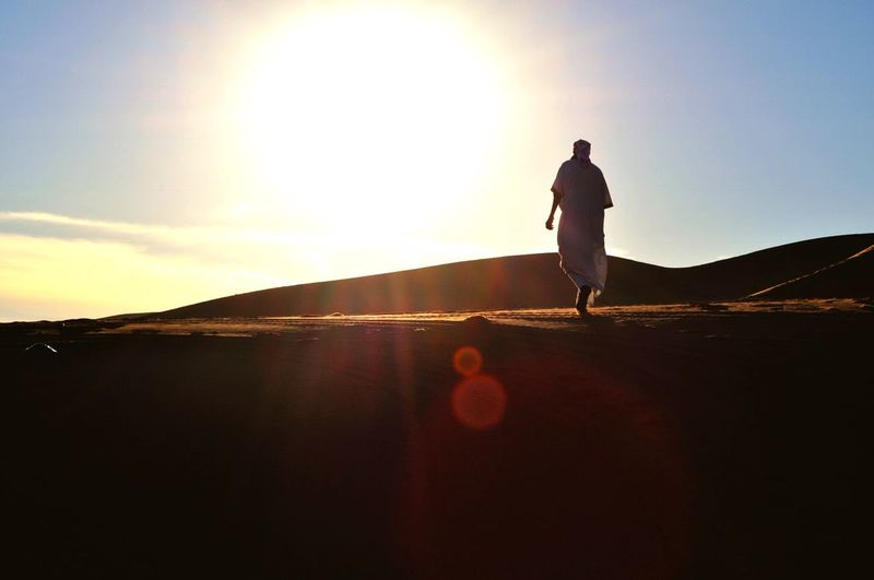 Spiritual walk into the sun Berber  Tradtional Dresss Alone Nostalgic Landscape Back Walking Alone... Sahara Desert Dune Sand Sky One Person Standing Sunset Real People Leisure Activity Nature Lens Flare Sunlight Lifestyles Beauty In Nature Sunbeam Outdoors Land EyeEmNewHere