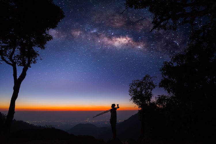 Silhouette of a Professional photographer who shooting a milky way on mountain ASIA Camera Thailand Tourist Travel Twilight Astronomy Astrophotography Backgrounds Beauty In Nature Galaxy Landscape Milky Way Mountain Night Outdoors Photography Professionalphotography Scenics - Nature Silhouette Sky Space Star Star - Space Tree The Traveler - 2018 EyeEm Awards
