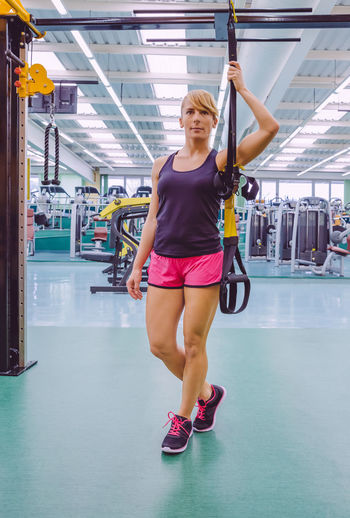 Full length of woman holding resistance band at gym