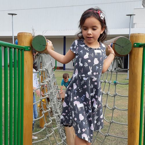 Cute girl on play equipment at park
