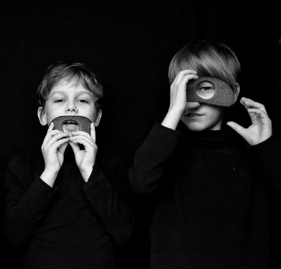 Portrait Of Siblings Holding Breads Against Black Background