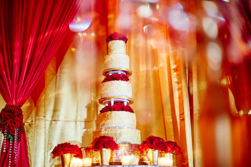 Luxury wedding cake with red roses and candle light decoration, The red gold curtain in background with some bokeh in foreground Banquet Gold Hinduism Indian Wedding Red Roses Setting Tradition Wedding Reception Arrangement Bouquet Celebration Close-up Curtain Decoration Event Food And Drink Illuminated Indoors  Luxury Marriage  Multi Colored Red Religion Temptation Wealth