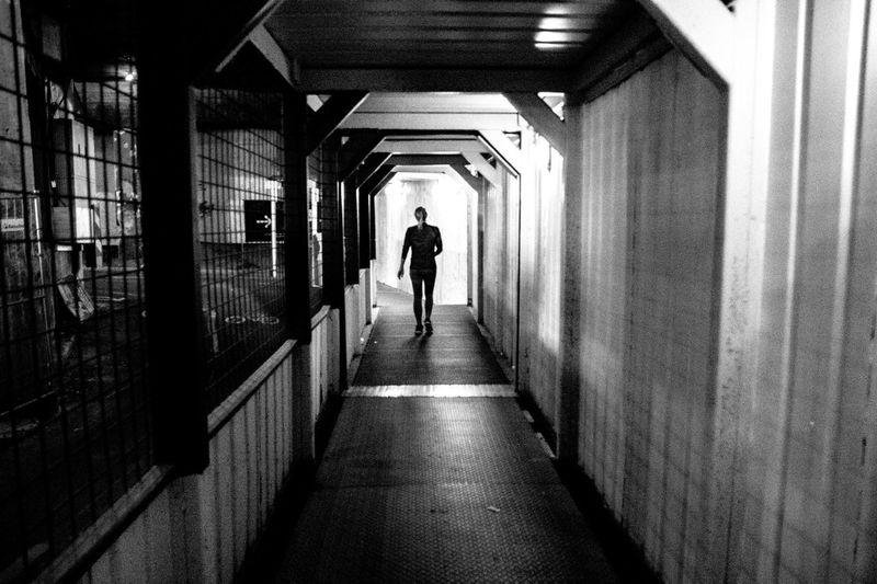 Rear view of man walking in tunnel