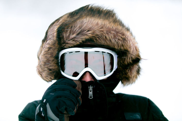 Portrait of woman wearing ski goggles against clear sky