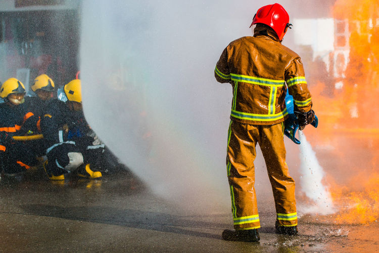 Accidents And Disasters Clothing Fire Hose Firefighter Full Length Headwear Helmet Heroes Men Occupation One Person Protection Protective Workwear Real People Rear View Rescue Worker Responsibility Safety Security Smoke - Physical Structure Spraying Standing Uniform Water Work Helmet