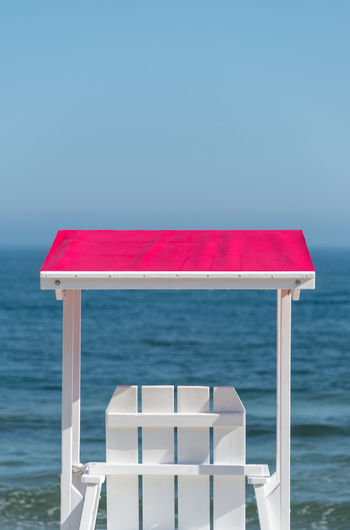 White lifeguard chair visible from the back with a pink visor against the background beautiful sea