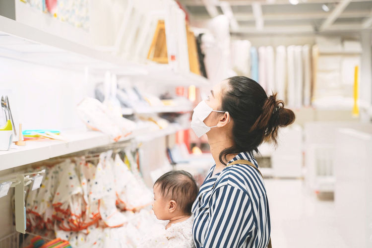 Side view of mother wearing mask with baby girl in store