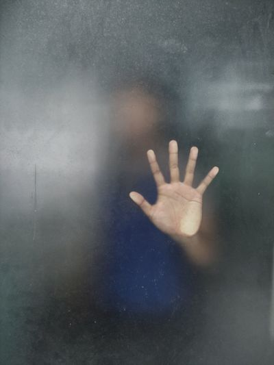 Close-up of hand on glass