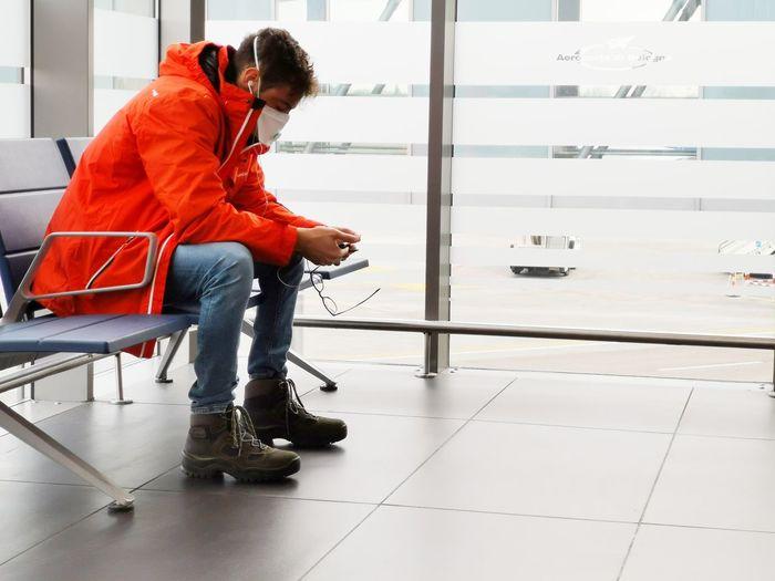 Man wearing mask using phone sitting on seat indoors