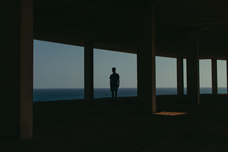 Silhouette man standing by window while looking at sea