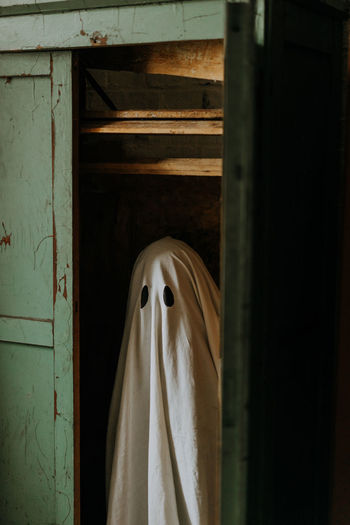 Little ghost standing in the closet. autumn halloween