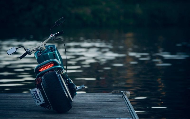Motorcycle parked on pier by lake