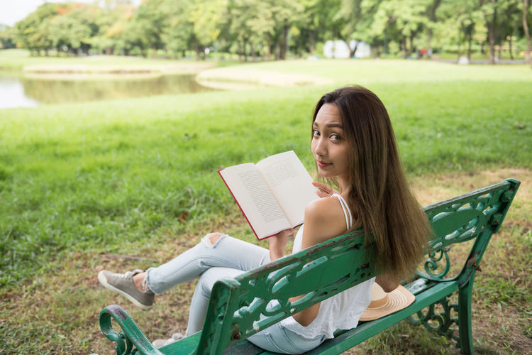Young woman sitting on book in field