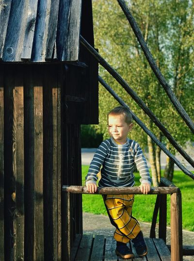 Boy standing on wooden house at park