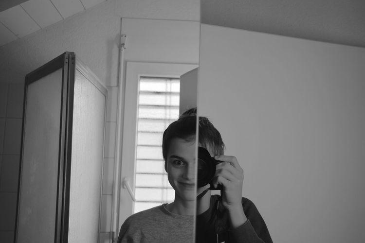 Smiling young man taking mirror selfie in bathroom