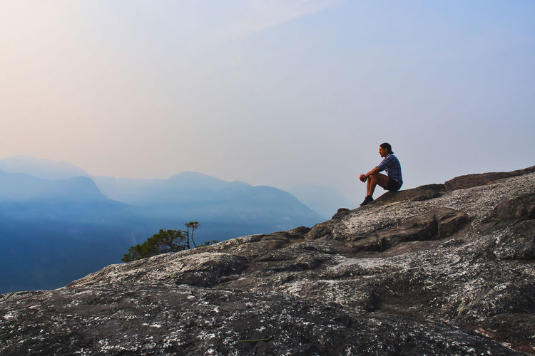 Side View Of Man Sitting On Cliff Against Sky