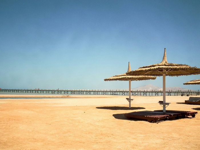 Beach Sharm El-Sheikh Umbrella Lounger Holiday Sea Sky Sand Sun No People Parasol Clear Sky Colour Image Copy Space Horizontal Nature Scenic Sunny Tranquil Scene Thatched Roof Summer Sunshine Outdoors Holiday Pier