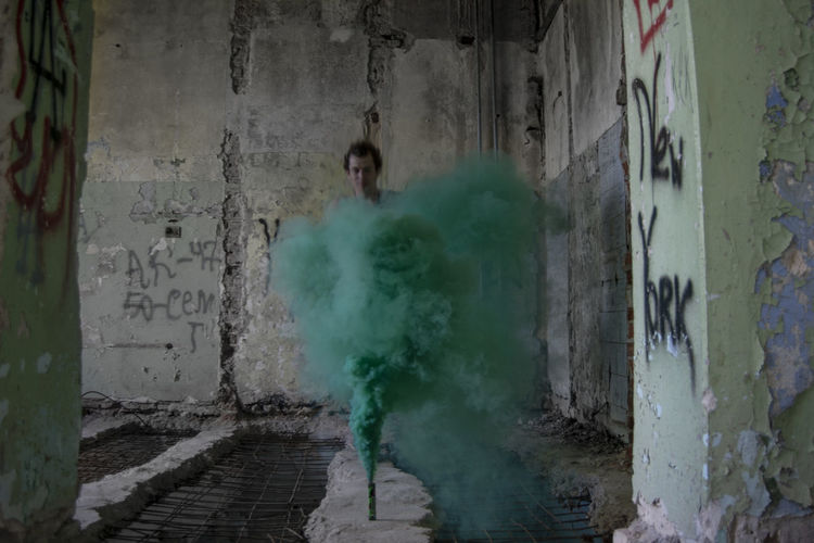 Smoke - Physical Structure Architecture Wall - Building Feature Day One Person Warning Sign Built Structure Green Color Real People Destruction Damaged Building Motion Indoors  Concrete Sign Smoke Smokescreen Colored Smoke Abandoned Abandoned Places Ephemeral Dissolve Green Color Green Smoke