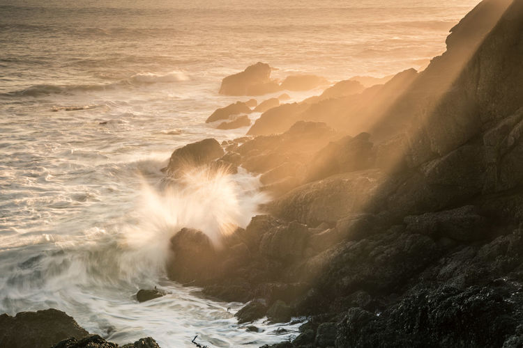 Waves breaking against sea during sunset