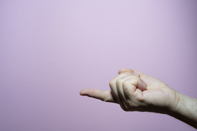 Close-up of person hand holding purple background