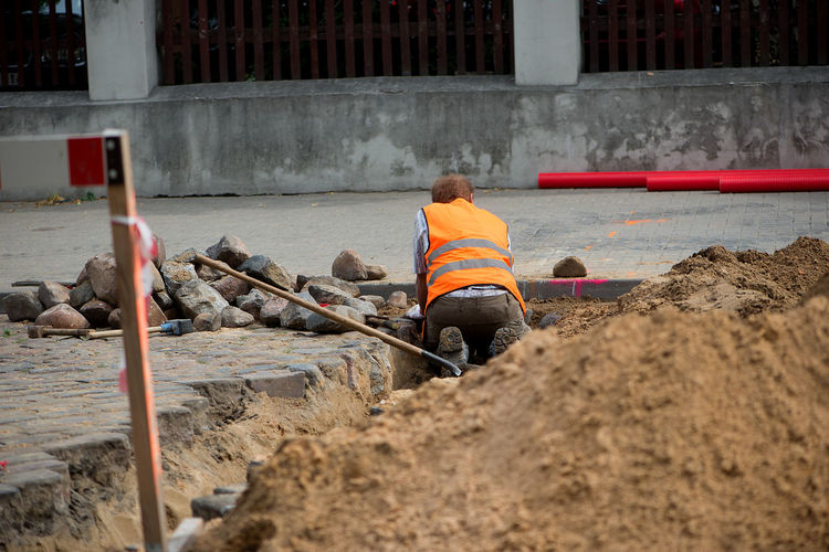 Rear view of construction worker digging on footpath