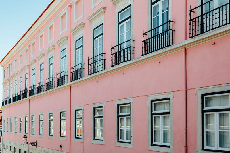 The pink facade Façade Aligned Architecture Building Building Exterior Built Structure City Day Glass - Material In A Row Low Angle View Multi Colored Outdoors Pink Color Repetition Residential District Side By Side Sky Streetphotography Style Window Windows