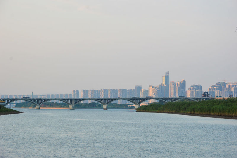 Bridge Over River With City In Background