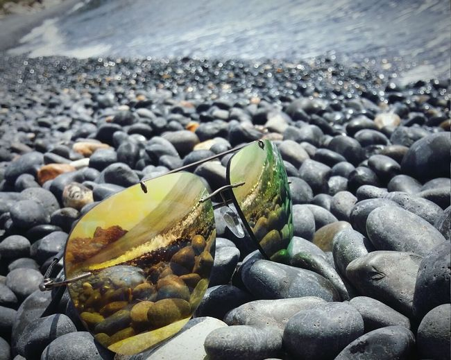 Close-Up Of Sunglasses On Pebbles At Shore