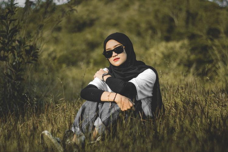 Young muslim woman wearing sunglasses sitting on field