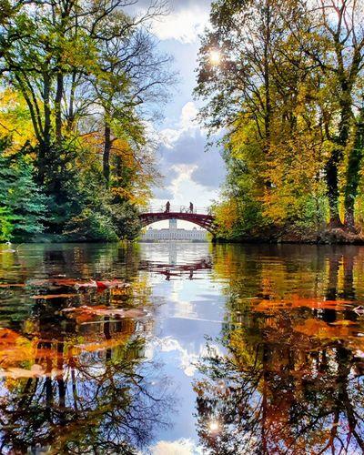 Arch bridge over lake against sky during autumn