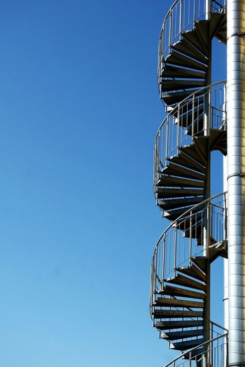 Low Angle View Of Fire Escape Against Clear Blue Sky