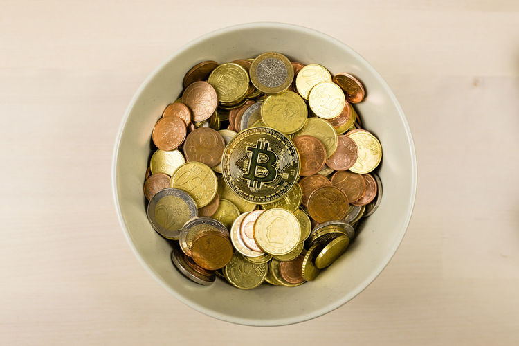 High angle view of coins in bowl on table