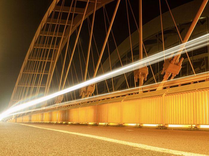 Light trails on bridge in city at night