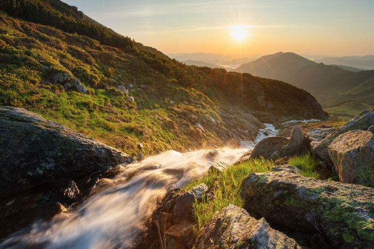Scenic view of stream amidst rocks against sky during sunset