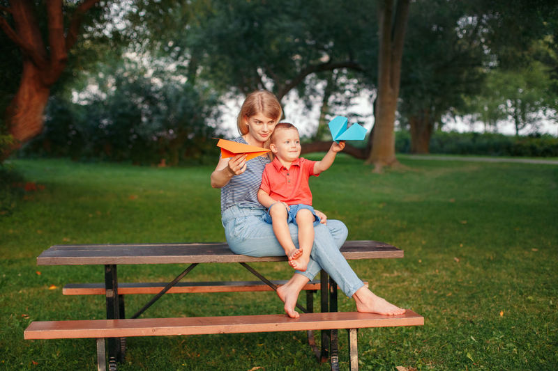 Smiling mother with boy sitting on bench in park