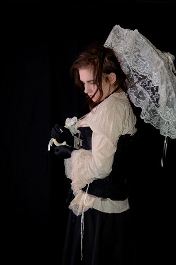 Young girl in steam punk look, holding white open umbrella, standing and looks down