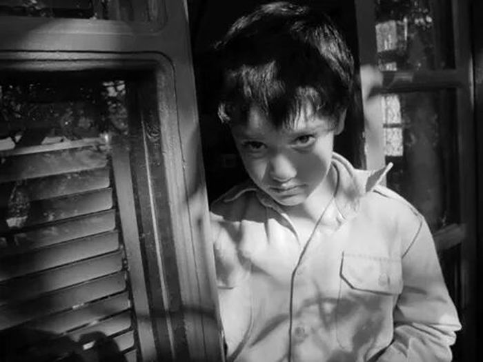 Close-Up Of Boy Standing By Window
