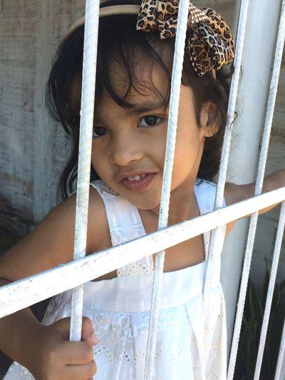 Portrait of cute girl standing looking through metal gate