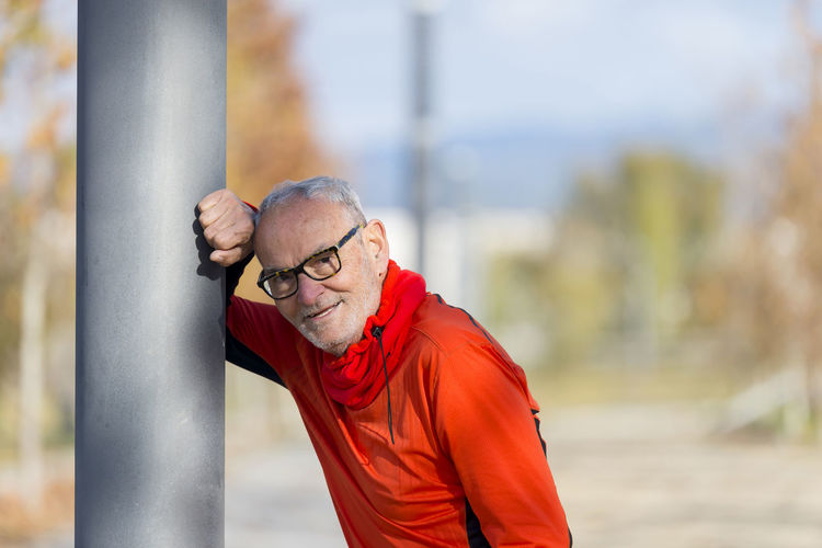 Handsome middle aged man in sports uniform looking at camera and smiling Man Day Eyeglasses  Eyeglasses  Focus On Foreground Healthy Lifestyles Lining Looking At Camera Male One Person Outdoor Photography Outdoors Park People Portrait Real People Red Runner Senior Adult Senior Men Senior Women Seniors Sports