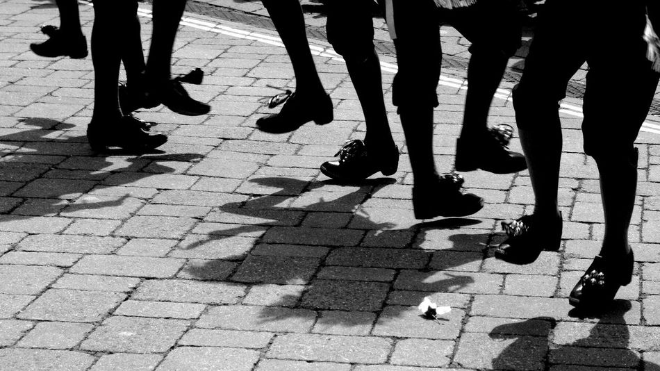 Dancing Folk Dance Footpath Footwear Friendship Human Foot Leisure Activity Lifestyles Low Section Medium Group Of People Men Outdoors Pavement Paving Stone Person Shadows Unrecognizable Person Up Close Street Photography People And Places. Monochrome Photography Black And White Friday