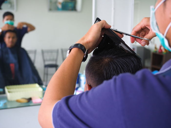 Cropped hands of hairdresser cutting man hair