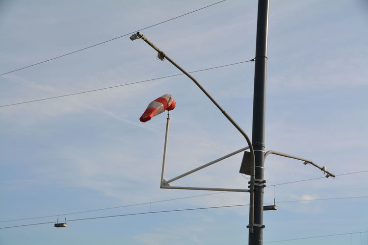 Low angle view of windsock on electricity pylon against sky
