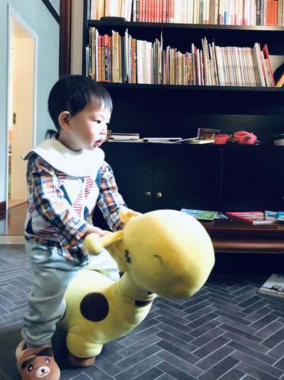 Cute baby girl sitting with toy