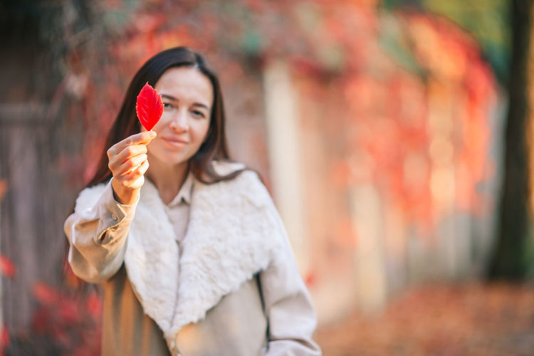 Portrait of woman holding ice cream standing outdoors during autumn